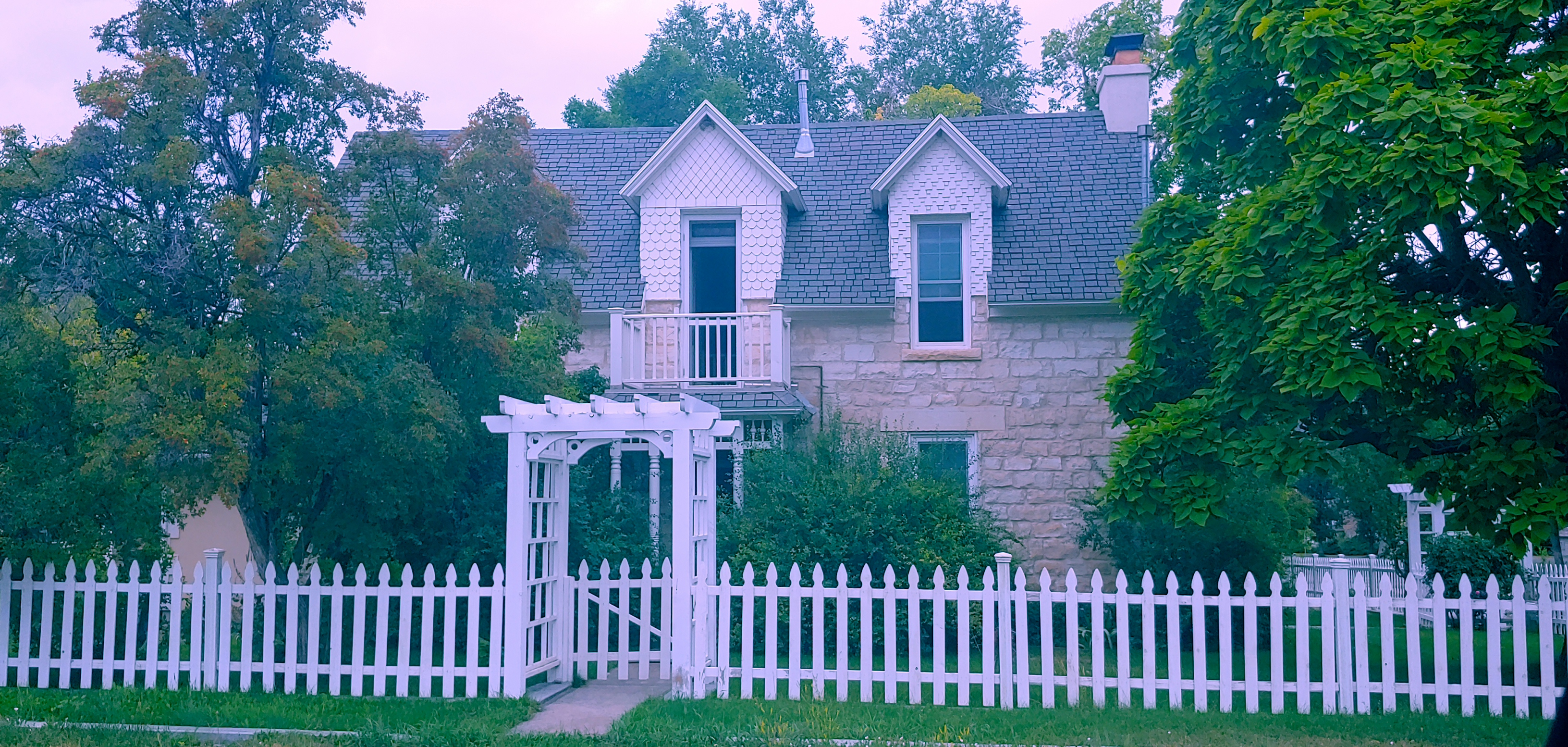 Stone home with white picket fence and trees